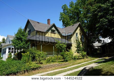 A yellow Victorian home with a wraparound porch on Division Street near downtown Petoskey, Michigan.