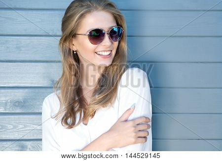 Portrait of beautiful young cheerful blonde woman with long hair wearing sunglasses and white shirt, wooden grey background behind her