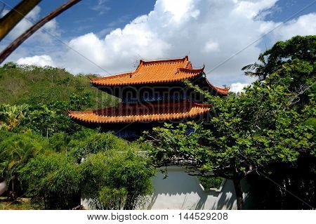 San Ya / Hainan China: Orange tiled roof with flying eaves set amidst groves of bamboo and tropical vegetation in the gardens at the Nanshan Temple *