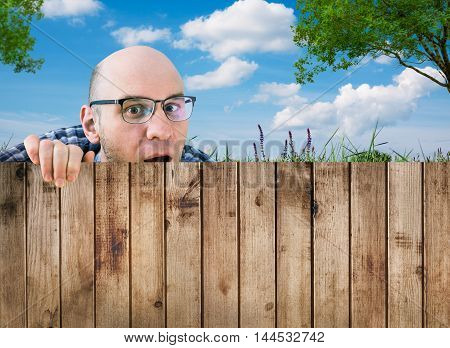 a nosey neighbor man looking over fence