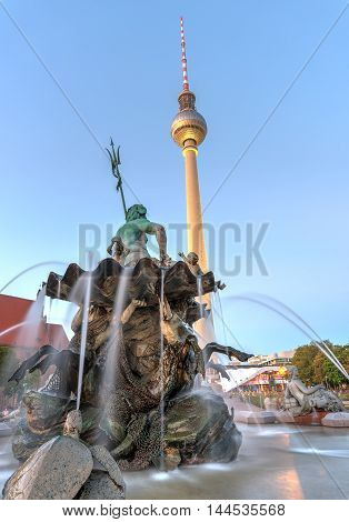 The Neptune fountain and the TV Tower in Berlin at twilight