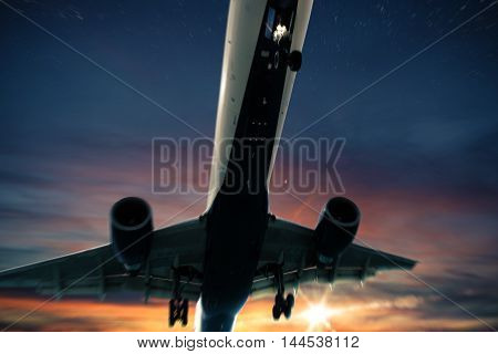 Aircraft flies in the sky at sunset