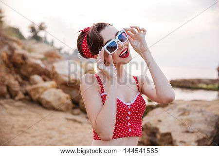 Smiling beautiful pinup girl in headband and suglasses having fun at the beach