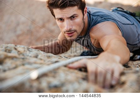 Man reaching for a grip while he rock climbs on a steep cliff poster