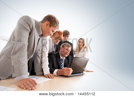 Wide angle shoot of business group of two young ladies, two young men and a mature boss at work
