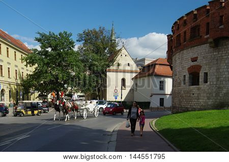 Krakow Poland - 25 August 2016: Podzamcze street. On the right side are the ramparts of Wawel Castle in the background you can see the church of St. Giles. Along the street goes cab rides to transport visitors.