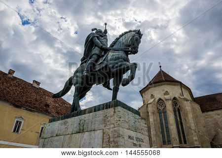 Statue of Michael the Brave in Citadel of Alba Iulia city in Romania. St. Michael's Cathedral on background