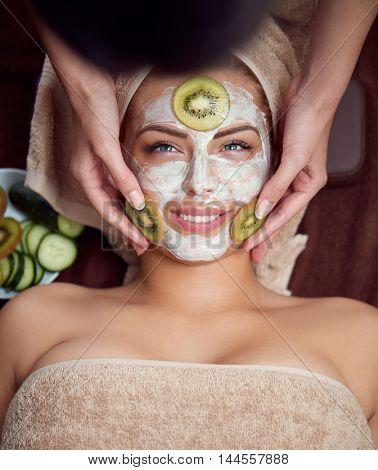 Treatment with kiwi mask on facial skin, beautiful girl in spa salon