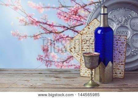 Passover matzo and wine on wooden vintage table over blossom tree background. Seder plate with hebrew text says bone and lettuce.