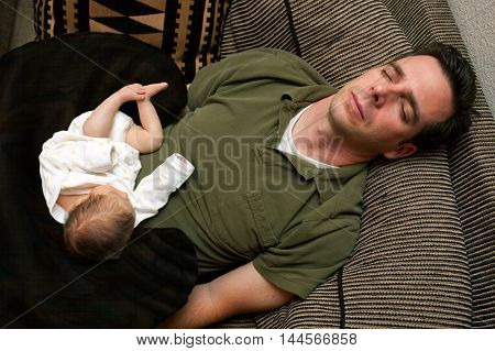 A newborn baby is curled up asleep on her sleeping father.