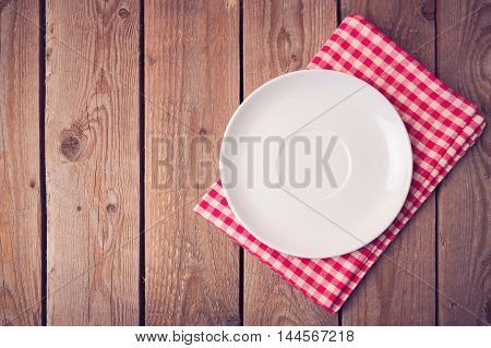 Plate on checked tablecloth over wooden background. View from above