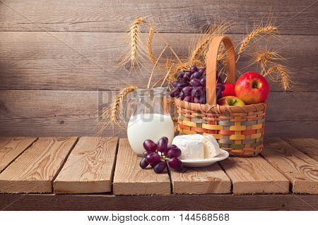 Jewish holiday Shavuot celebration. Basket with fruits and milk over wooden background