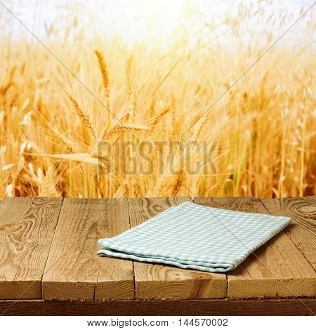 Checked tablecloth on wooden deck table over wheat field background