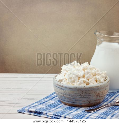 Cottage cheese and jug with milk on white wooden table. Jewish holiday Shavuot concept