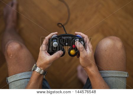 Gothenburg, Sweden - January 25, 2015: A shot from above of a young man's hands holding a black game pad controller for the Nintendo GameCube video game console developed by Nintendo Co., Ltd.