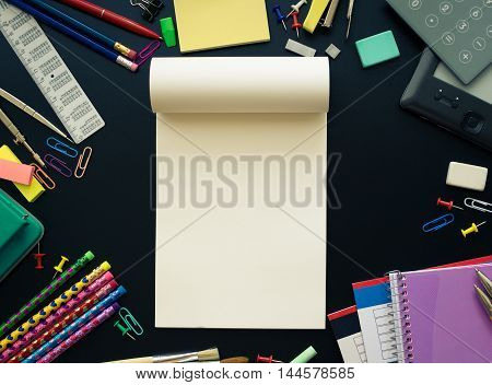 Back to school concept. Notebook and school supplies with calculator and ebook on blackboard background with space for text. Back to school concept with stationery. Top view.