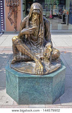SKOPJE MACEDONIA - SEPTEMBER 17: Beggar Sculpture in Skopje on SEPTEMBER 17 2012. Poor Old Man Bronze Statue in Downtown Skopje Macedonia.