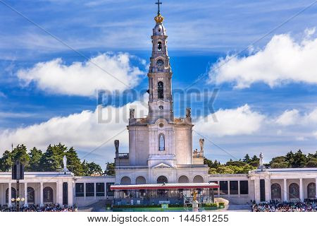 May 13th Celebration of Mary's Appearance Basilica of Lady of Rosary Bell Tower Fatima Portugal. Church created on site where three Portuguese Shepherd children saw Virgin Mary of the Rosary. Basilica created in 1953. Statement in back is about Invovled i