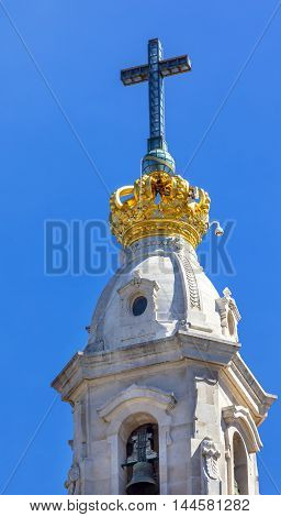 Basilica of Lady of Rosary Bell Tower Golden Crown Cross Fatima Portugal. Church created on site where three Portuguese Shepherd children saw Virgin Mary of the Rosary. Basilica created in 1953.