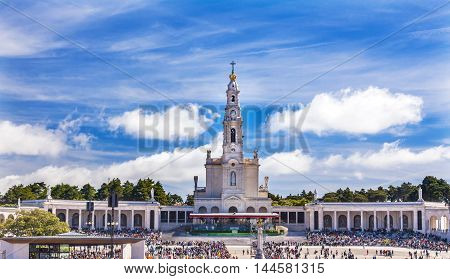 May 13th Celebration of Mary's Appearance Basilica of Lady of Rosary Bell Tower Fatima Portugal. Church created on site where three Portuguese Shepherd children saw Virgin Mary of the Rosary. Basilica created in 1953. Statement in back is about God and Lo