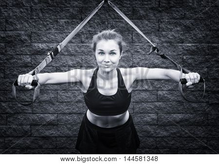 Young attractive woman does suspension training with fitness straps outdoors -- toned picture