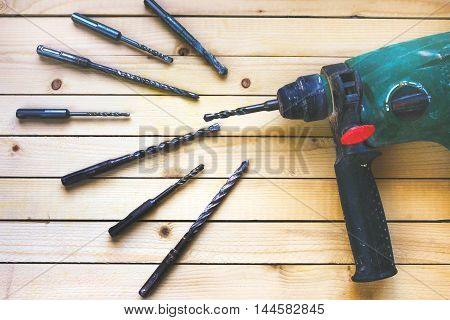 Electric hammer drill lies on a wooden table with drill