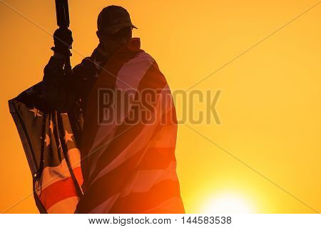 True Patriot Soldier. American Soldier with Assault Rifle Covered by United States Flag.