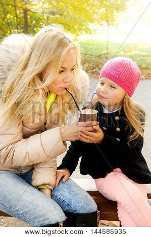 Happy young mother with daughter have a fun drinking a milkshake from the one paper cup using two tubes, autumn outdoor