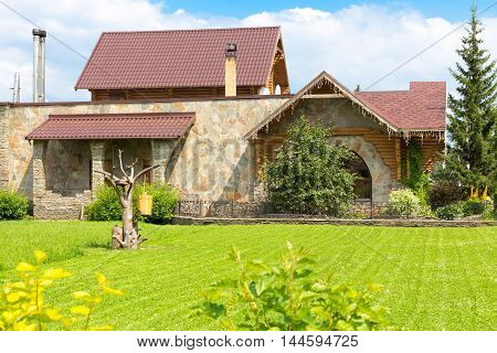 large stone house with a house of logs on the roof with a large half-shorn lawn
