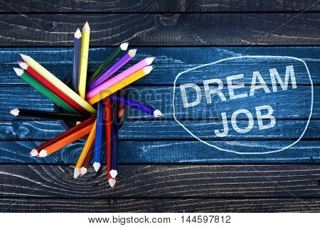 Dream Job text painted and group of pencils on wooden table