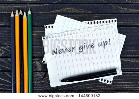 Never give up text on notepad and office tools on wooden table