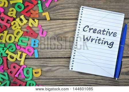 Creative Writing text on notepad and magnetic letters on wooden table