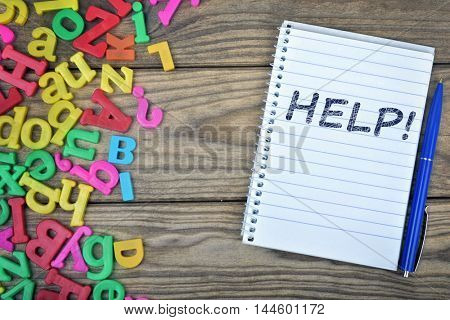 Help text on notepad and magnetic letters on wooden table