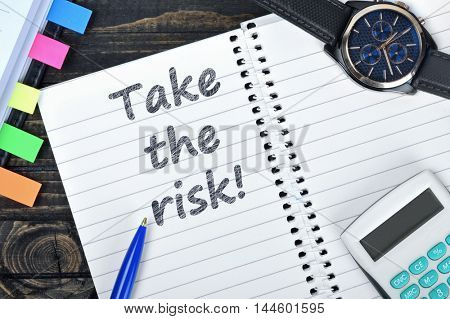 Take the risk text on notepad and watch on desk