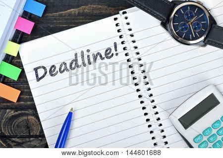 Deadline text on notepad and watch on desk