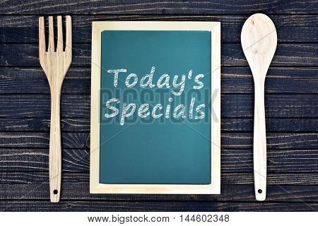 Today's Specials text on green board with fork and spoon on wooden table