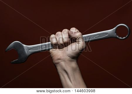 Male hand holding wrench, red background. Strong man holding mechanic tool. Handyman, professional worker concept