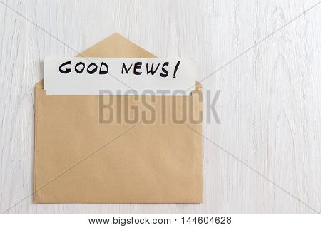 Opened yellow envelope with paper letter inside on white wooden background, copy space. Good news note in brown cover, mockup