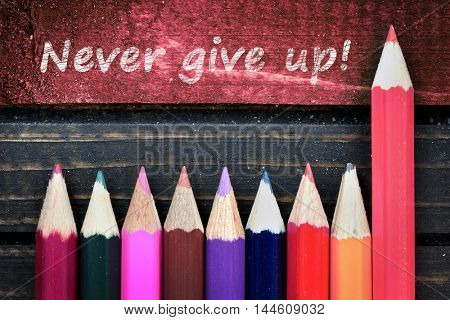 Never give up text and group of pencil on wooden table