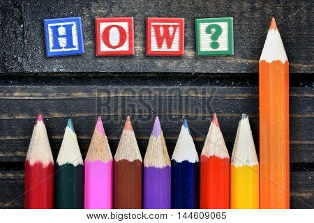 How? question text and group of pencil on wooden table
