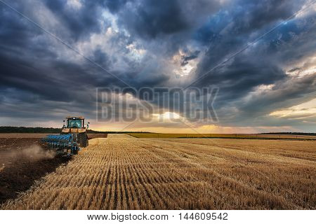 Farmer in Tractor with Plough Plowing in a Field