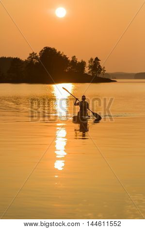 Paddle-boarding on peaceful and quiet lake during sunset