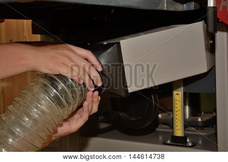 Person plugged suction hose to planer - closeup