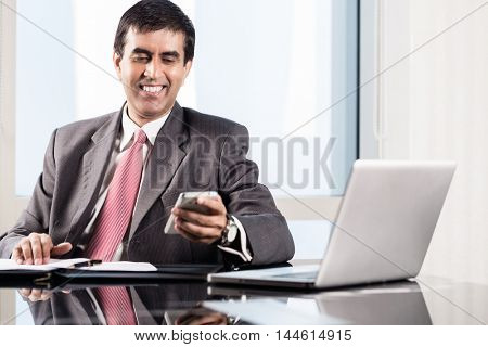 Indian CEO of company in his business office at desk, reading text on smartphone