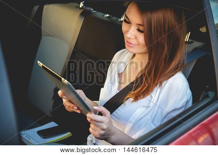 Young, beautiful woman sitting in the back seat of a car with a tablet in hands