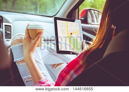 Girl with tablet in her hands traveling in a car using online gps map for direction.