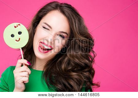 Cheerful pretty woman holding a candy winks laughs shows language. Brunette girl fashionable and stylish on a pink background in Studio. Beauty, laughter, fun.