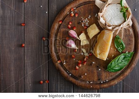 Cheese delikatessen closeup on rustic wood. Wooden desk with parmesan, camembert and brie cuts decorated with garlic, pomegranate and rosemary, top view image with copy space