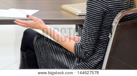 Sexy female beauty attending a meeting where she is taking notes.