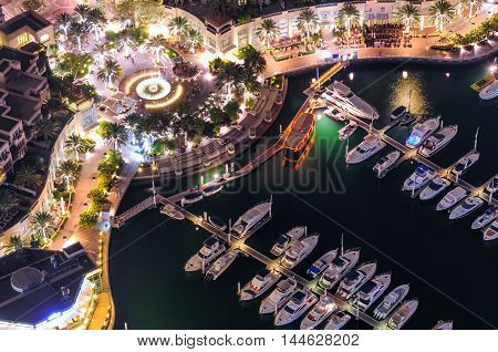Amazing Colorful Dubai Marina Fountain And Yacht Dock During Night. Beautiful Sidewalk Among Tallest
